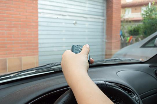 pressing remote control to enter the car park