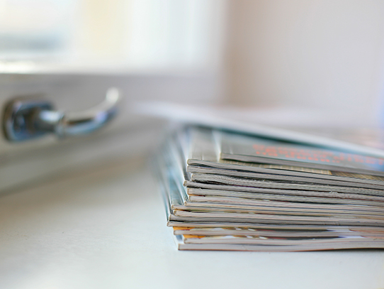 Pile of magazines on  white window sill with latch